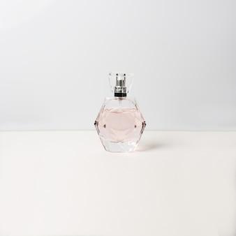 Bottiglia di profumo sulla superficie bianca