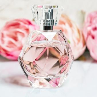 Bottiglia di profumo con fiori su superficie chiara
