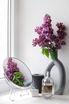 Bottiglia di profumo con fiori lilla su sfondo bianco. composizione con specchio. fiori che sbocciano