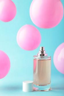 Bottiglia di profumo con palloncini rosa sull'azzurro. vista dall'alto