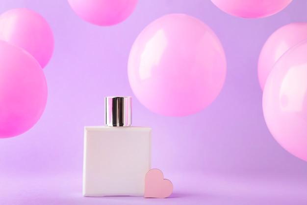 Bottiglia di profumo con palloncini rosa su rosa. vista dall'alto
