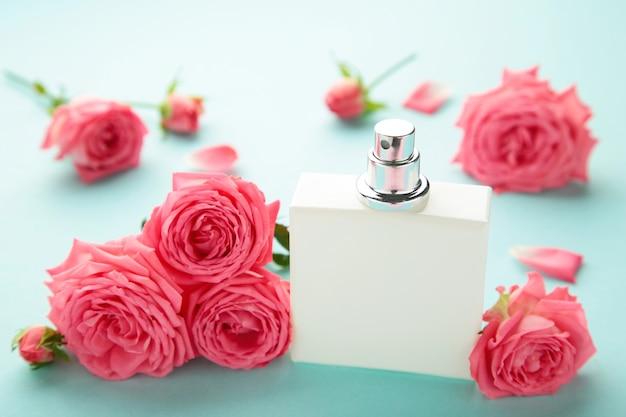Bottiglia di profumo con rose rosa sul blu