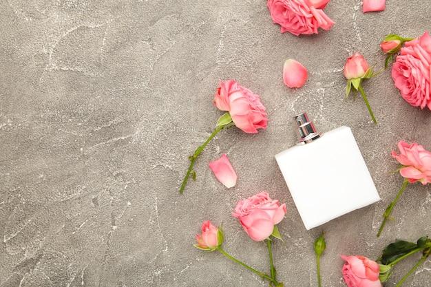 Bottiglia di profumo con rose rosa su grigio