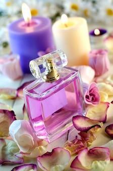Bottiglia di profumo con petali di rose rosa. trucco moda e prodotti per la cura del corpo.