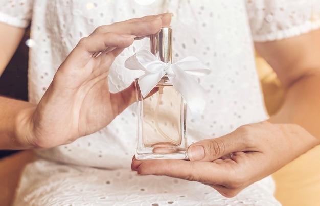 Bottiglia di profumo con un nastro regalo bianco in una mano femminile sullo sfondo di una ragazza in un abito bianco in colori chiari pastello. eau de toilette, eau de parfum, concetto di bellezza.