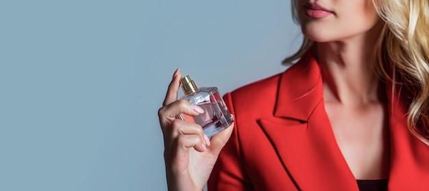Aroma spray donna bottiglia di profumo. donna che tiene una bottiglia di profumi. la donna presenta la fragranza dei profumi. womans con bottiglia di profumo. bella ragazza che usa il profumo. donna con bottiglia di profumo.