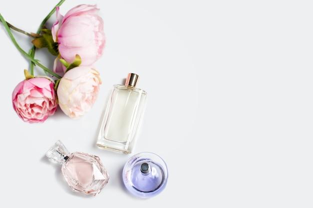 Bottiglie di profumo con fiori su superficie chiara. profumeria, cosmetica, collezione di fragranze