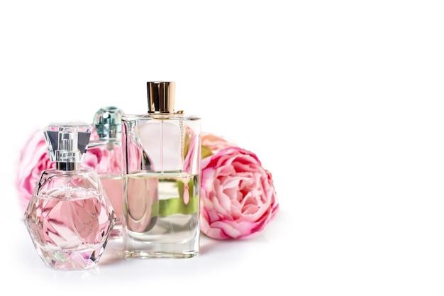 Bottiglie di profumo con fiori su superficie chiara