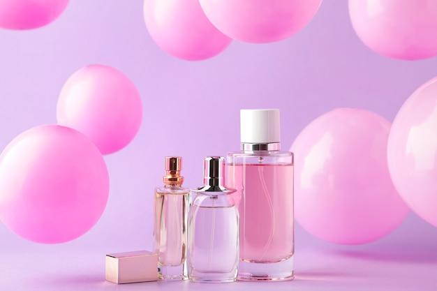 Bottiglie di profumo con palloncini rosa su rosa. vista dall'alto