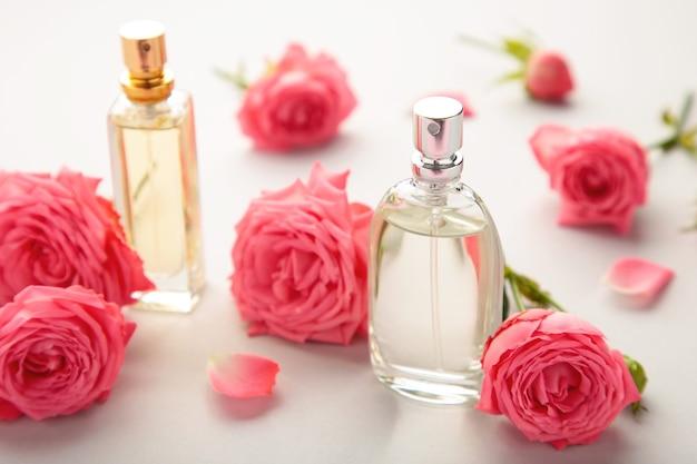 Bottiglie di profumo con rose rosa su grigio. vista dall'alto
