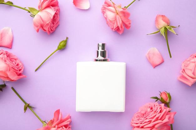 Bottiglie di profumo con rose rosa su viola. vista dall'alto