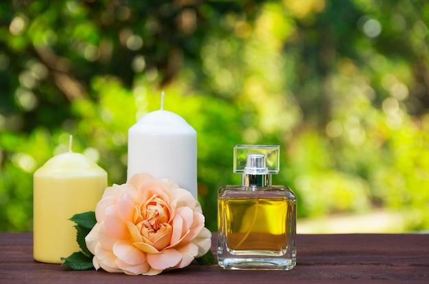 Profumo, candele e fiori su sfondo verde sfocato