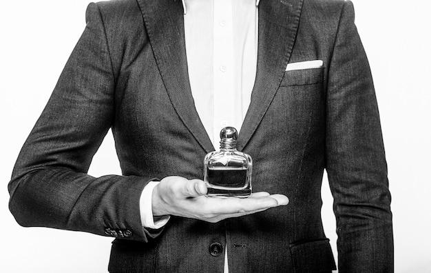 Profumo o bottiglia di colonia e profumeria, cosmetici, bottiglia di profumo, colonia maschile. maschio che sostiene il profumo della bottiglia bianco e nero