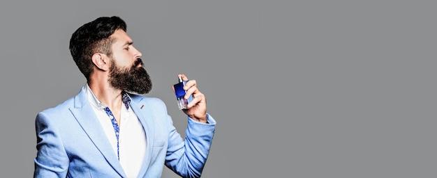 Profumo o bottiglia di colonia e profumeria, cosmetici, bottiglia di profumo, colonia maschile. profumo maschile, uomo barbuto in completo. profumo maschile, uomo barbuto in completo. copia spazio.