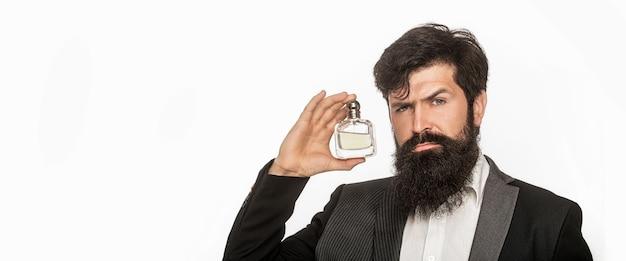 Bottiglia di profumo o colonia, profumeria, cosmetici, bottiglia di colonia profumata, colonia di contenimento maschile. profumeria maschile, uomo barbuto in completo. maschio che sostiene una bottiglia di profumo. spazio per il testo.