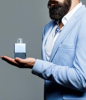 Bottiglia di profumo o colonia, profumeria, cosmetici, bottiglia di colonia profumata, colonia di contenimento maschile. profumeria maschile, uomo barbuto in completo. maschio che sostiene una bottiglia di profumo.