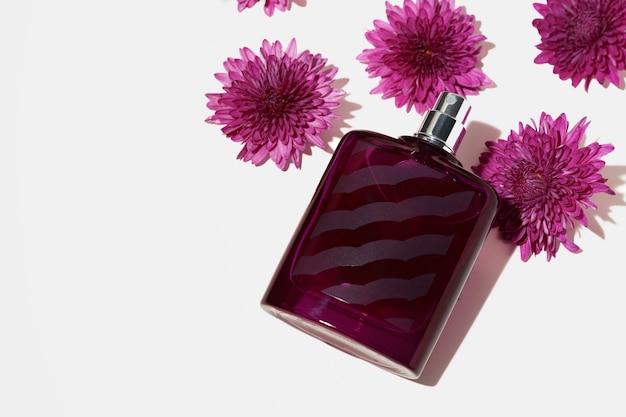 Bottiglia spray di profumo e piccoli fiori su sfondo grigio si chiudono