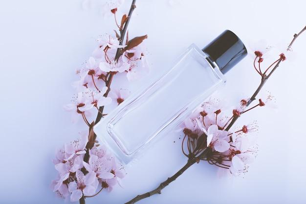 Profumo con fiori rosa sul tavolo bianco