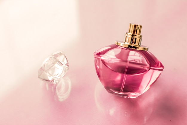 Profumeria spa e concetto di branding bottiglia di profumo rosa su sfondo lucido profumo floreale dolce profumo glamour e eau de parfum come regalo di festa e design di marca di cosmetici di bellezza di lusso