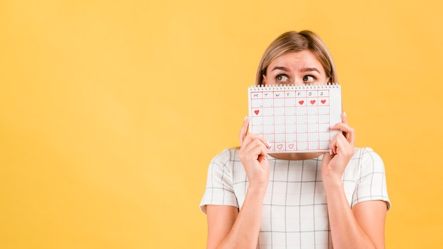 Calendario periodo con forme di cuore disegnati e donna che copre il viso