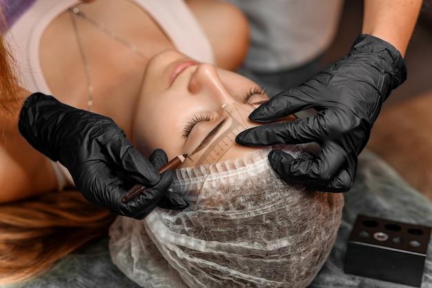 Trucco permanente della fronte nel salone di bellezza, primo piano. estetista professionista segna la lunghezza delle sopracciglia con la matita e un righello di misurazione sopracciglio speciale. trattamento di cosmetologia