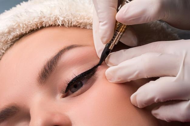 Trucco occhi permanente close up shot. cosmetologo che applica il tatuaggio degli occhi.
