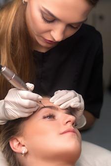 Trucco permanente per sopracciglia. cosmetologo che applica il tatuaggio delle sopracciglia.