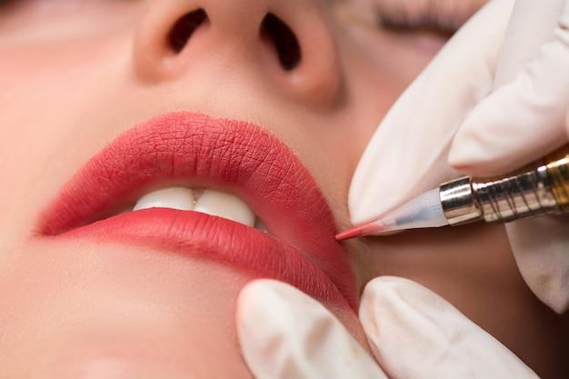 Procedura di trucco permanente, da applicare sulla ragazza. trucco labbra nel salone di tatuaggi. riprese da vicino.