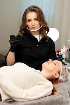 Uno specialista del trucco permanente in un salone di bellezza prepara il cliente per la procedura