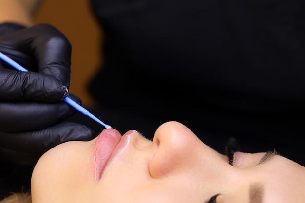 Il truccatore permanente tiene in mano un micro pennello e distribuisce l'anestesia lungo il contorno delle labbra della modella