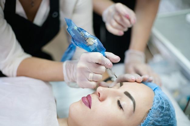 Corso di trucco permanente. colpo ritagliato di estetista stagista che insegna come utilizzare la macchina per tatuaggi per il microblading delle sopracciglia.