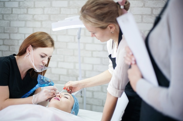 Corsi di trucco permanente. estetista femminile che utilizza una macchina per tatuaggi per il microblading delle sopracciglia.