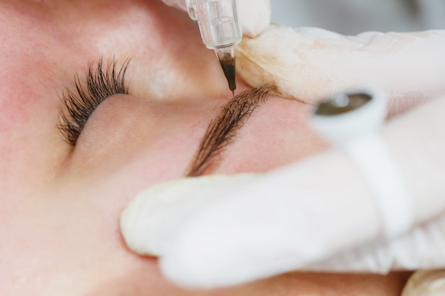 Trucco permanente, tatuaggio delle sopracciglia. cosmetologo nell'applicazione bianca dei guanti compone con la macchina per la donna nel salone di bellezza