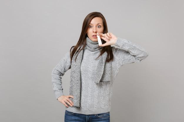 Giovane donna perplessa in maglione grigio, tenuta della sciarpa facendo uso delle gocce nasali isolate sul fondo grigio della parete in studio. stile di vita sano, trattamento delle malattie malate, concetto di stagione fredda. mock up copia spazio.