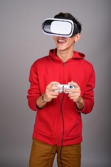 Ragazzo adolescente persiano utilizzando occhiali vr e controller di gioco per la realtà virtuale