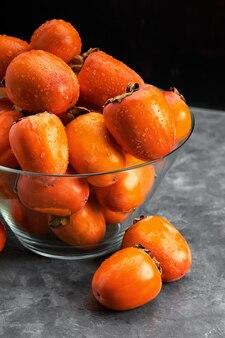 Frutti di cachi con gocce d'acqua su sfondo nero