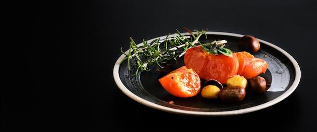 Fette di cachi e cachi, ramo di rosmarino su un piatto nero, fuoco selettivo