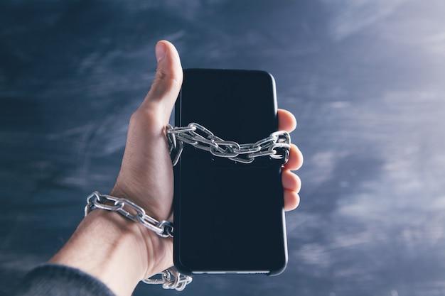 Persona incatenata a uno smartphone