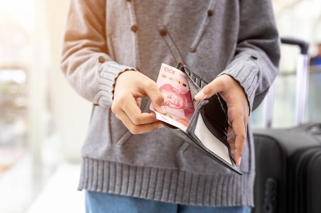 Persona che controlla le banconote in portafoglio nero