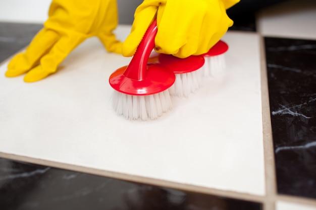 Una persona che pulisce il pavimento di un bagno con un guanto di gomma giallo