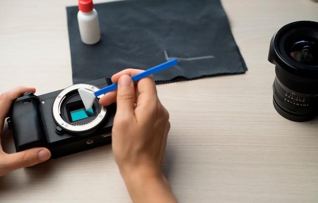 Persona che pulisce il sensore della fotocamera digitale mirrorless con il primo piano del tampone con. concetto di tecnologia