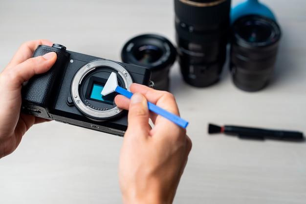 Persona che pulisce la fotocamera digitale mirrorless con tampone e lente.