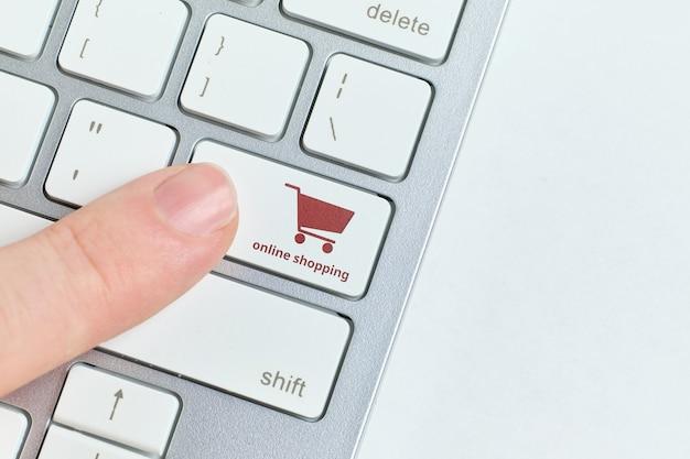 La persona fa clic su un pulsante della tastiera per lo shopping online.