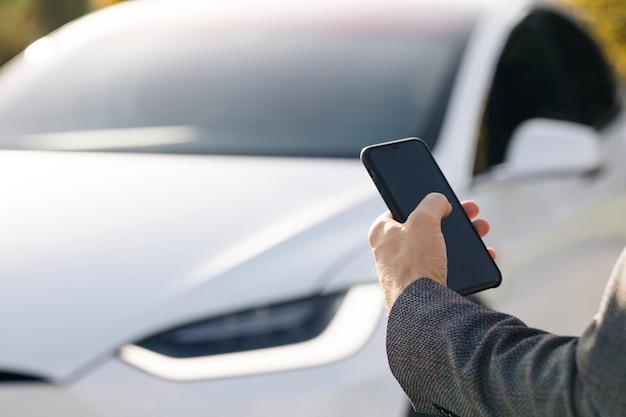 La persona controlla un'auto elettrica a guida autonoma utilizzando l'applicazione mobile