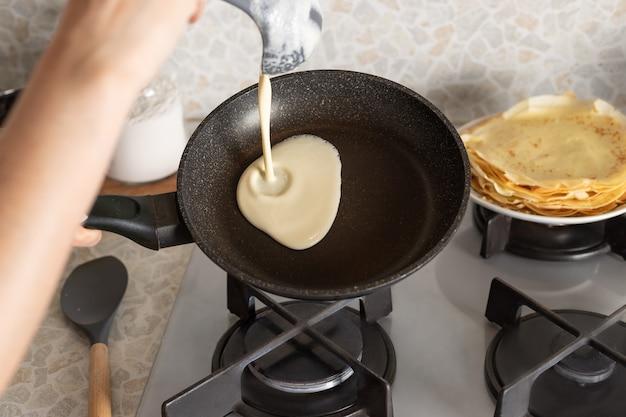 Persona che cucina frittelle sottili sulla padella in cucina