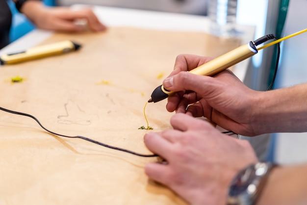 Persona che crea con penna con manico 3d, adolescente che utilizza la moderna penna da stampa.