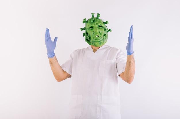 Persona travestita da coronavirus con maschera in lattice virus covid19, indossa tuta da dottore, braccia aperte, su sfondo bianco