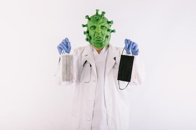 Persona travestita da coronavirus con il virus covid19 della maschera in lattice, che indossa una tuta da dottore in possesso di maschere chirurgiche su sfondo bianco