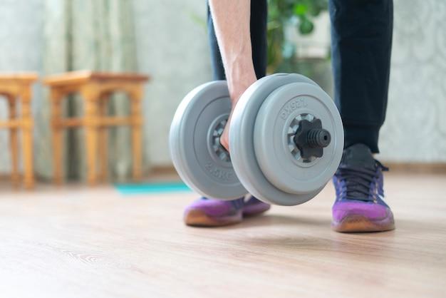 Persona che fa allenamento a casa con alcune attrezzature con manubri