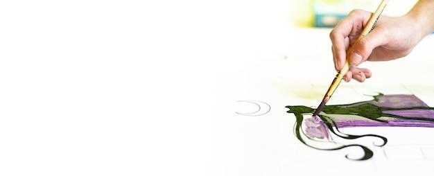Una persona disegna con un pennello e dipinge su una grande tela in uno studio d'arte. artista creativo e moderno di belle arti, un capolavoro di disegno, formazione sul disegno, scuola d'arte, corsi di disegno a distanza, banner